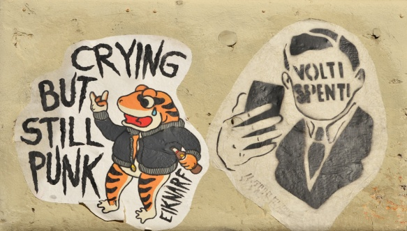 two slaps on a wall, one is a frog standing upright with a bottle in one hand and the words crying punk, by artist eiknarf. the other is a black stencil of a man with blank face taking a selfie on his phone. Instead of facial features he has the words volti spenti which are Italian
