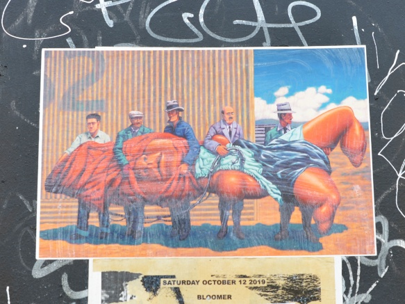 a street art poster on a wall, 5 men carrying something orange