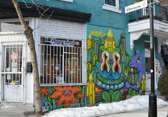 bookstore on a corner in Montreal, white window frame with bars on window, a mural by waxhead beside the window