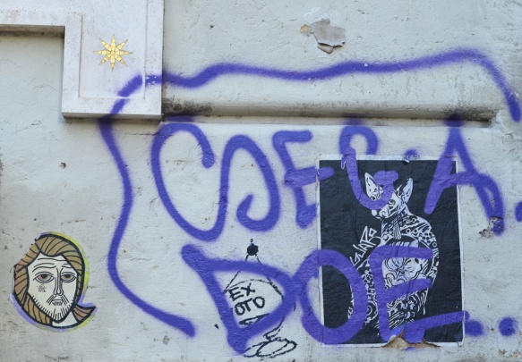 black and white cat poster paste up by guaro and a jesus head with the words tifa toro