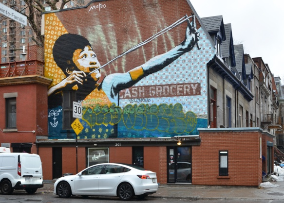 mural of a boy with a slongshot by mateo on the side of cash and grocery store on Milton St in Montreal