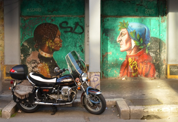 motorcycle parked in front of a wall with a mural by Mauro Sgarbi, green background, called Divine Welcome, Dante on one side, an immigrant woman on the other