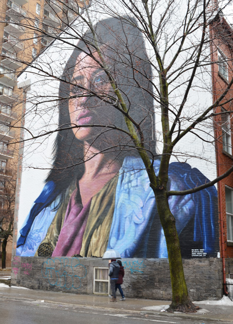 large mural of a woman from shoulders up, wearing blue jacket over olive and pink tops, long brown hair, a tree with no leaves is in front, two people walking past on the sidewalk