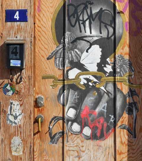 wood door with blue number 4 and 4 on a mailbox, with pasteups on the door too