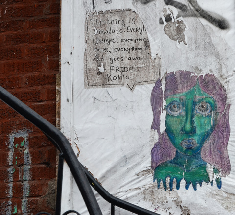 a green face with purple hair paste up beside a paper with words on it about Frida Kahlo