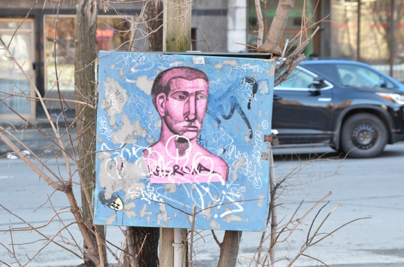 a paste up of a pink man's head and torso on a blue metal box, short hair, middle aged man