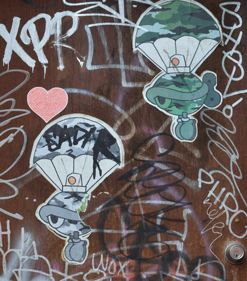 two turtle cap paste ups on a door with a red heart between them