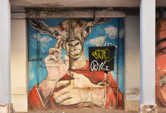 a mural of a person shoulders up except that there is a goat's head instead of a human head, arms and hands are human, wearing a red shirt,