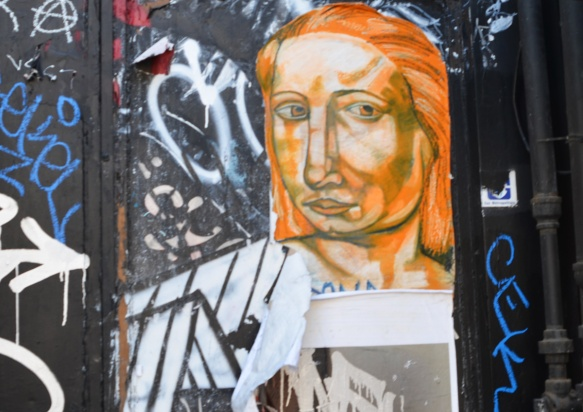 an orange face pasteup on a black exterior wall