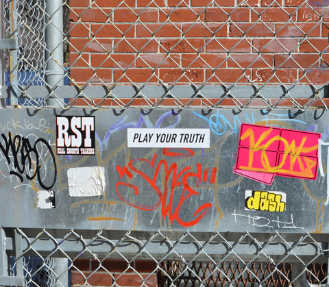 stickers on a metal gate, including one with the words play your truth