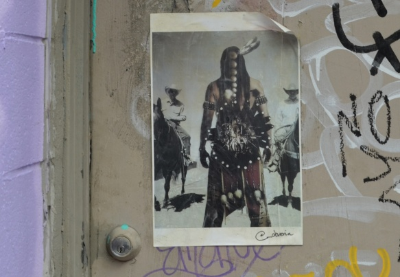 a street art poster on a door of cowboys and indian