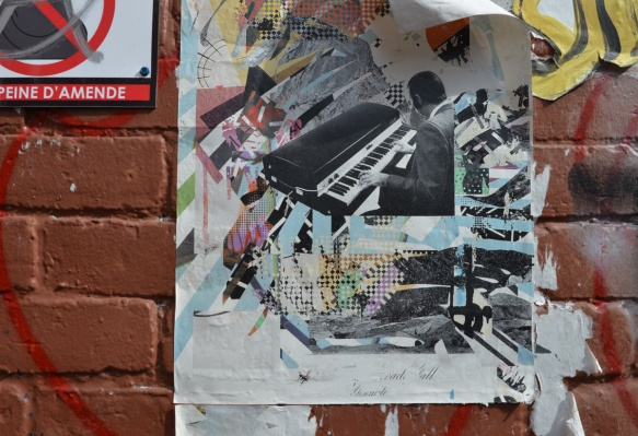 paper poster on a wall outside, man playing a keyboard, musician,