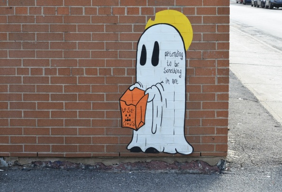paper pasteup of a ghost costume, white sheet, with black eyes, also little hands holding an orange bag. words on the ghost saying pretending to be something i'm not