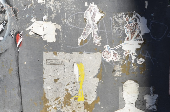 some old faded and partially torn wheatpaste paste ups on a grey wall