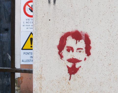 a red stencil on a concrete wall of a man with goatee
