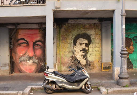 motorcycle parked in front of two mural of men's faces. one on the left is a just face, man with mustache called Gaetano. The other is an older man with Italian words written around him