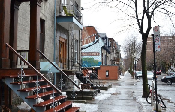 street in Montreal with stairs leading to front doors of houses, some snow, a mural on the side of building that you can see part of