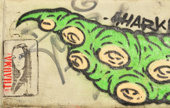 a long green lizard tail graffiti with a picture of a woman thauma beside