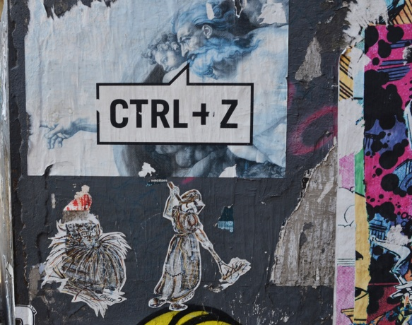 graffiti on a wall. one is a poster of Michelangelo's sistine chapel creation where god points finger at man, but this time, ctrl + z is written on top, the computer shortcut for undo. There are also two little drawings by L J S 57, women working, women in old fashioned clothing, one is sorting straw and the other is sweeping