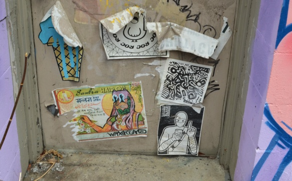 six wheatpaste graffiti papers on the lower part of a door, all in different conditions, an ice cream cone, an urban ninja squadron tbonez on his phone and a waxhead piece
