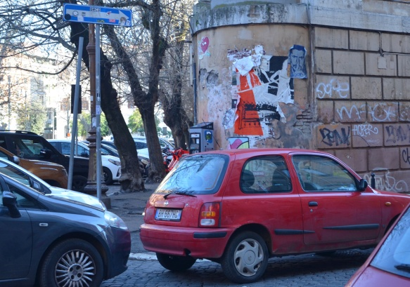 looking across traffic to a curved wall on a corner with graffiti on it