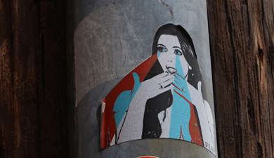 sticker on a pole, woman with laser lights coming out of her eyes,