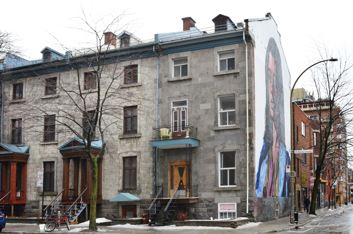 a large mural of a woman on the side of a row of old stone houses