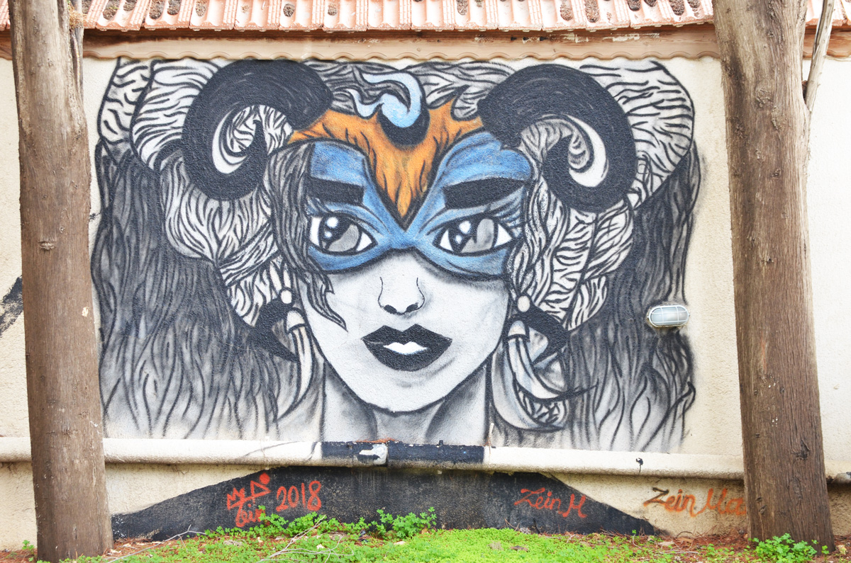 a painting by Zein of a woman's head, wearing blue eye mask, with curved horns