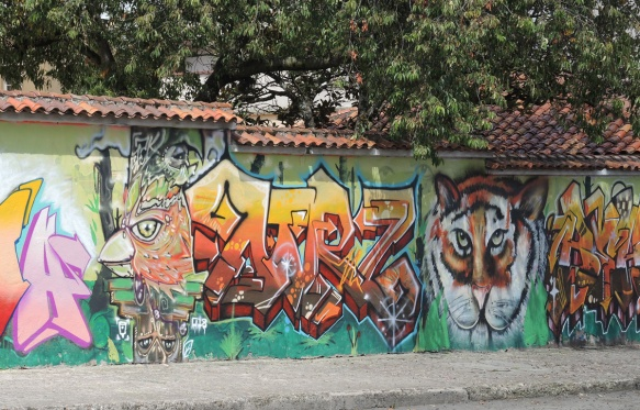mural on a wall with a large tiger head as well as the head of a bird, also two throw-ups, text,