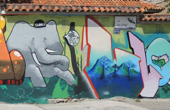 a grey elephant with a baseball cap that says Cuenca on it, also letters, possibly L and L, mural on a wall,