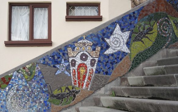 mosaics on a wall beside the stairs, white star, blue star, church, and a black insect