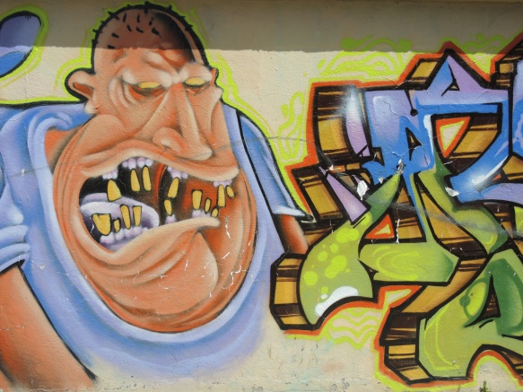 mural, picture of a  yelling man with mouth wide open showing crooked teeth, balding, overweight,