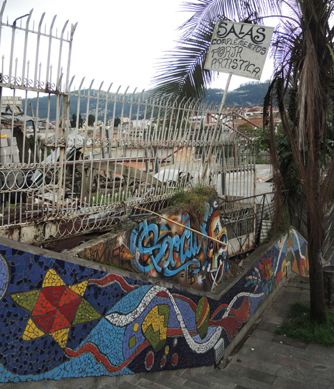 staircase outside, wall is covered with mosaics, with city beyond a wrought iron fence