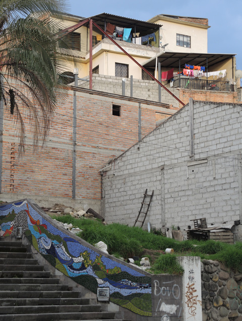 city houses on a hill with stairs below, mosaics on the wall
