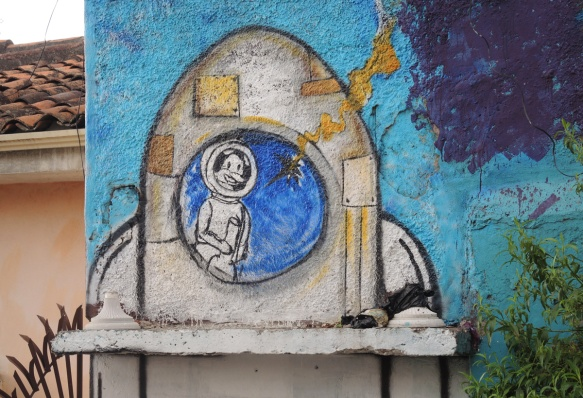 street art painting of an astronaut with a helmet on inside the round window of a rocket