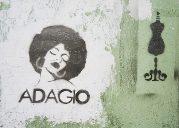 portrait of a woman, stencil in black, eyes closed, head tilted, round head of hair, words say adagio, also a stencil of a dressmaker's form