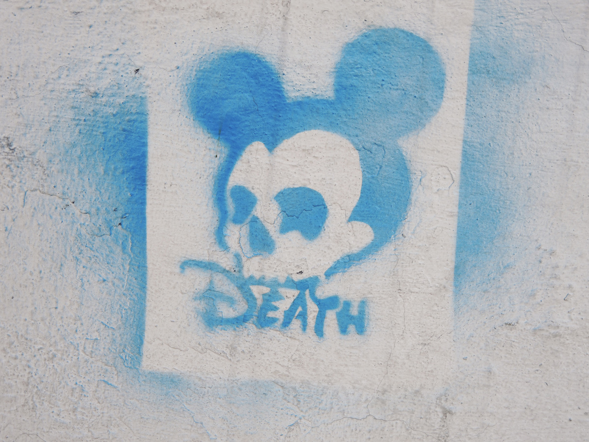 blue stencil of mickey mouse but with skull-like face with the word death under it, disney equated with death
