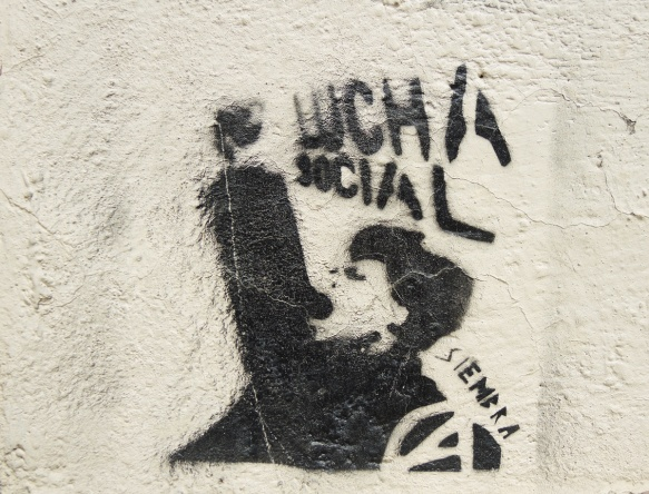 graffiti stencil in black of a man with fist upraised and open mouth, words lucha social