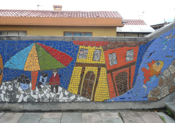 mosaics, 3 scenes, one is people under an umbrella, 2 houses one red and one yellow, and a fish swimming in a creek