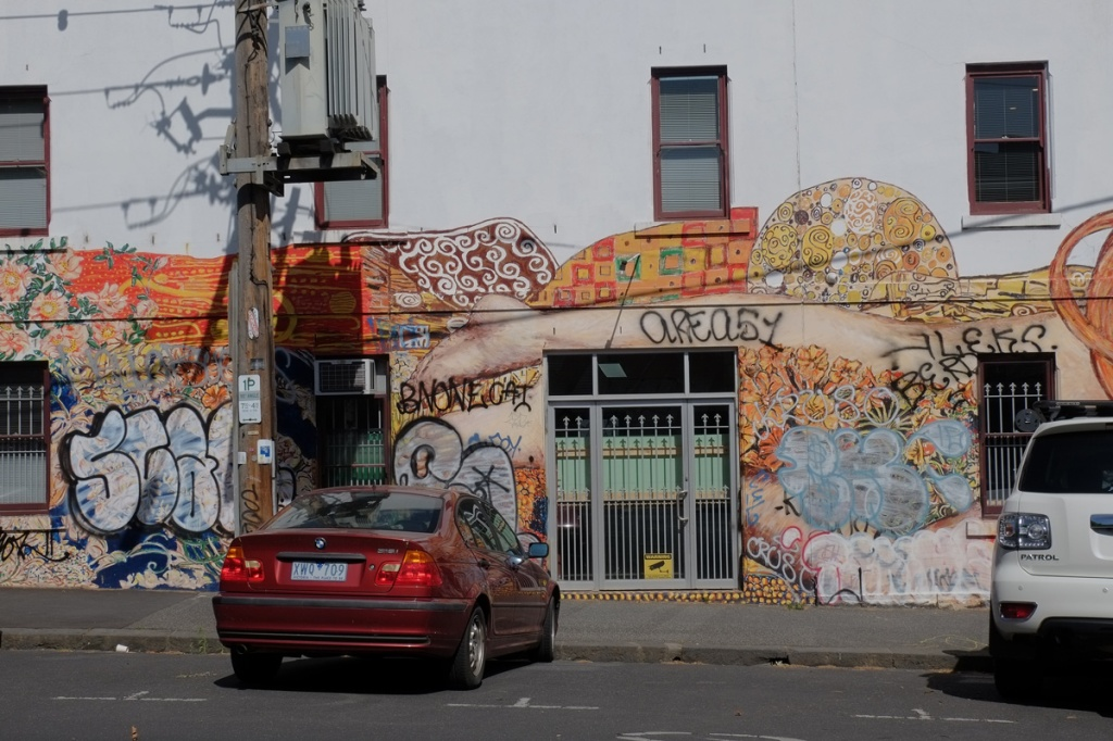 legs of naked woman in mural above windows in the building.  cars parked in front of it